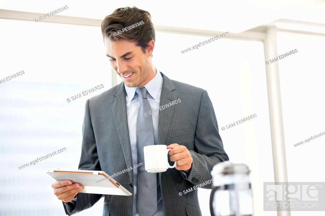 Stock Photo: Businessman drinking coffee and looking down at digital tablet.