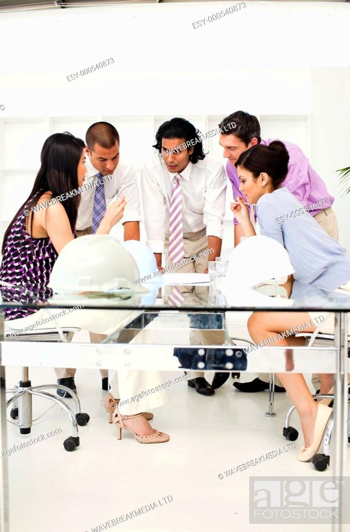 Stock Photo: A group of architects and their manager discussing blueprints in a meeting.