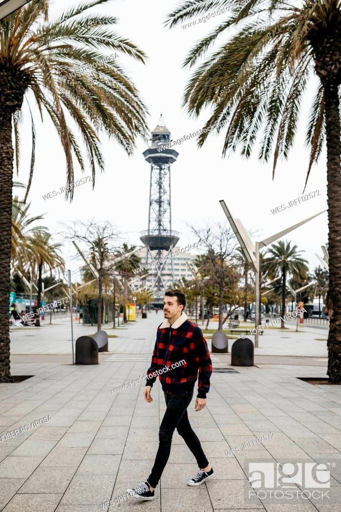 Photo de stock: Spain, Barcelona, Young man with casual clothes walking on a square.
