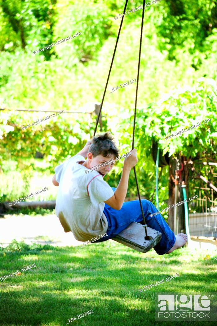 Stock Photo: Young boy making faces while swinging.