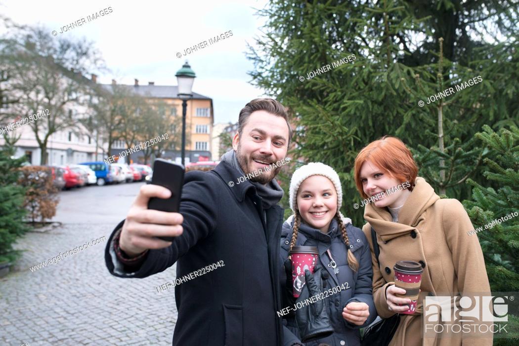 Stock Photo: Man with teenage girls taking selfie.