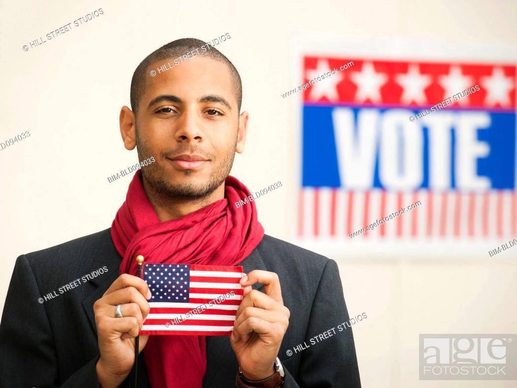 Stock Photo: Hispanic man holding American flag with Vote sign in background.