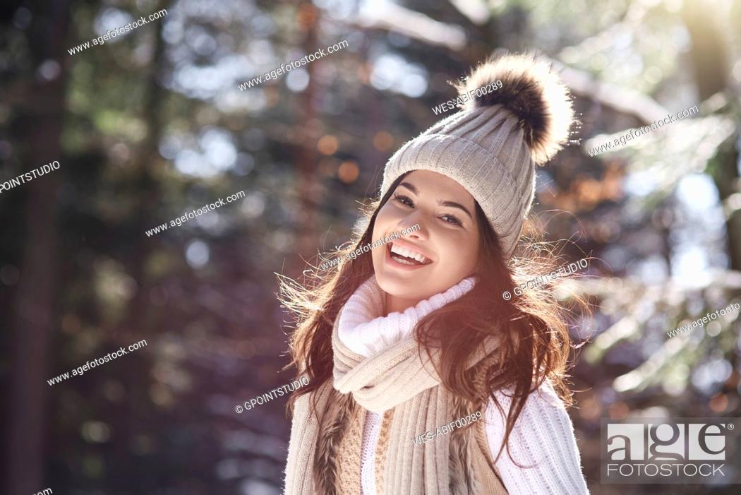 Imagen: Portrait of laughing young woman wearing knitwear in winter forest.