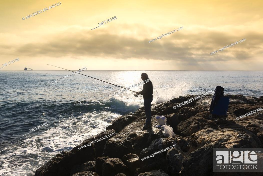 Stock Photo: Savona, Italy. A fisherman standing with the fishing rod in his hand, he is on the rocks at sunset, near him buckets and equipment in bags.