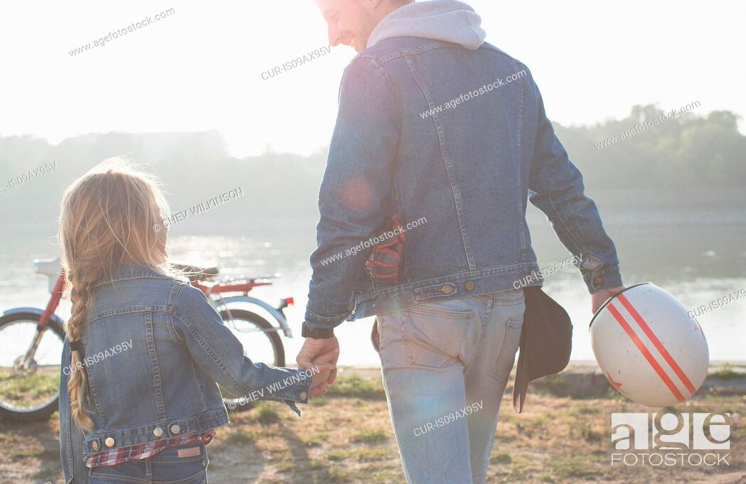 Imagen: Father and daughter, holding hands, beside lake, rear view.