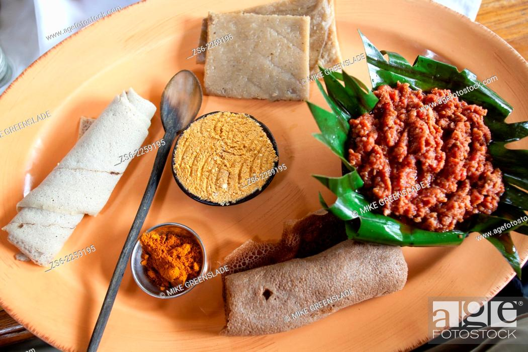 Imagen: Traditional Ethiopian meal of 'Kitfo' served with cottage cheese, banana bread, chilli powder and injera.