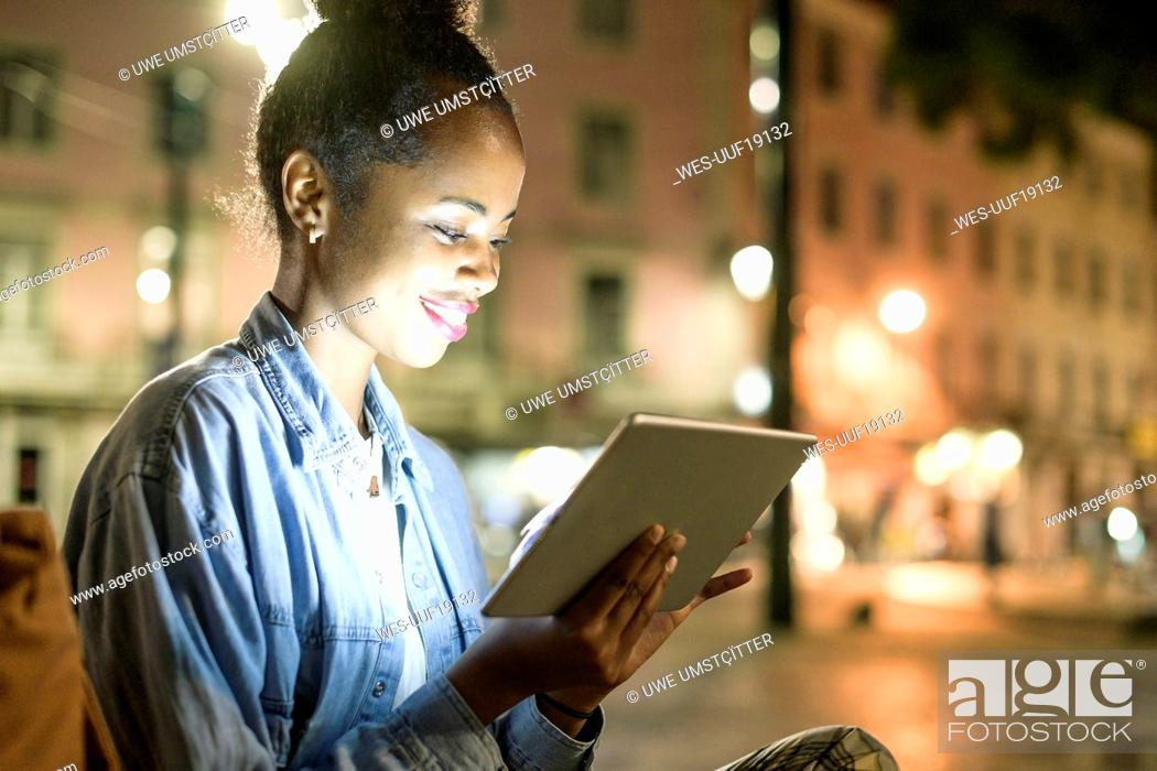 Stock Photo: Smiling young woman using digital tablet in the city by night, Lisbon, Portugal.