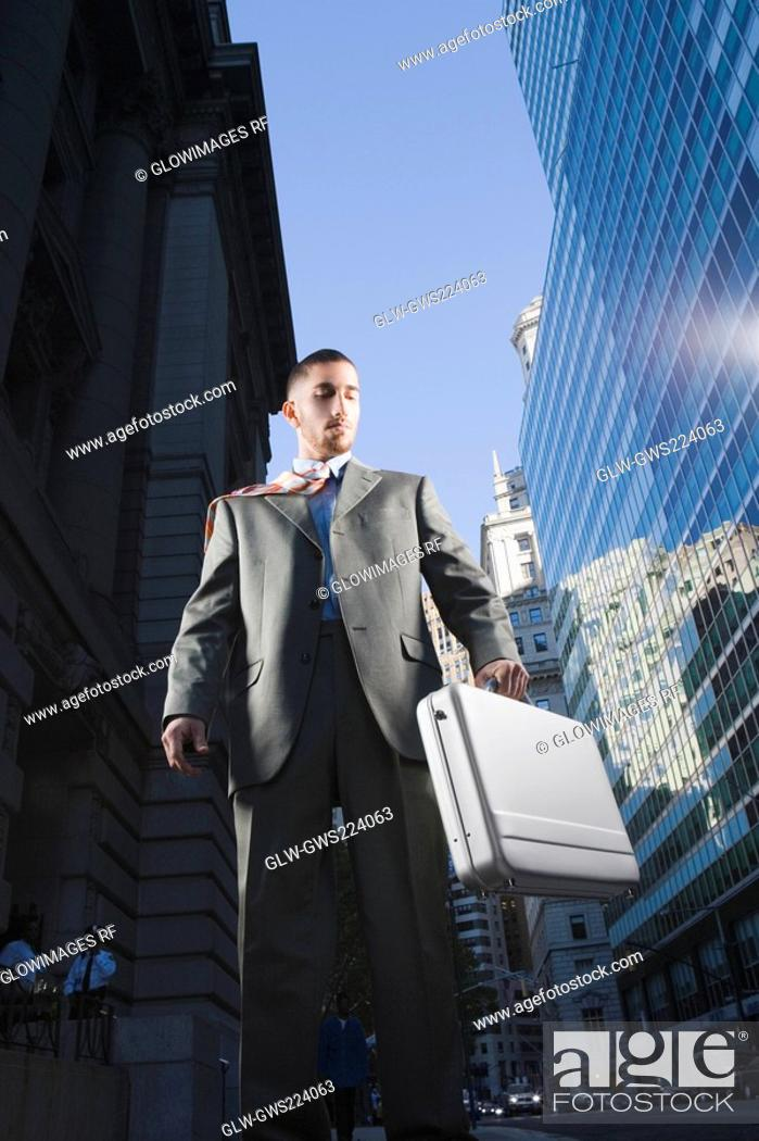 Stock Photo: Low angle view of a businessman holding a briefcase.