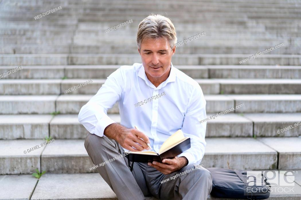 Stock Photo: Mature businessman sitting on stairs looking at notebook.