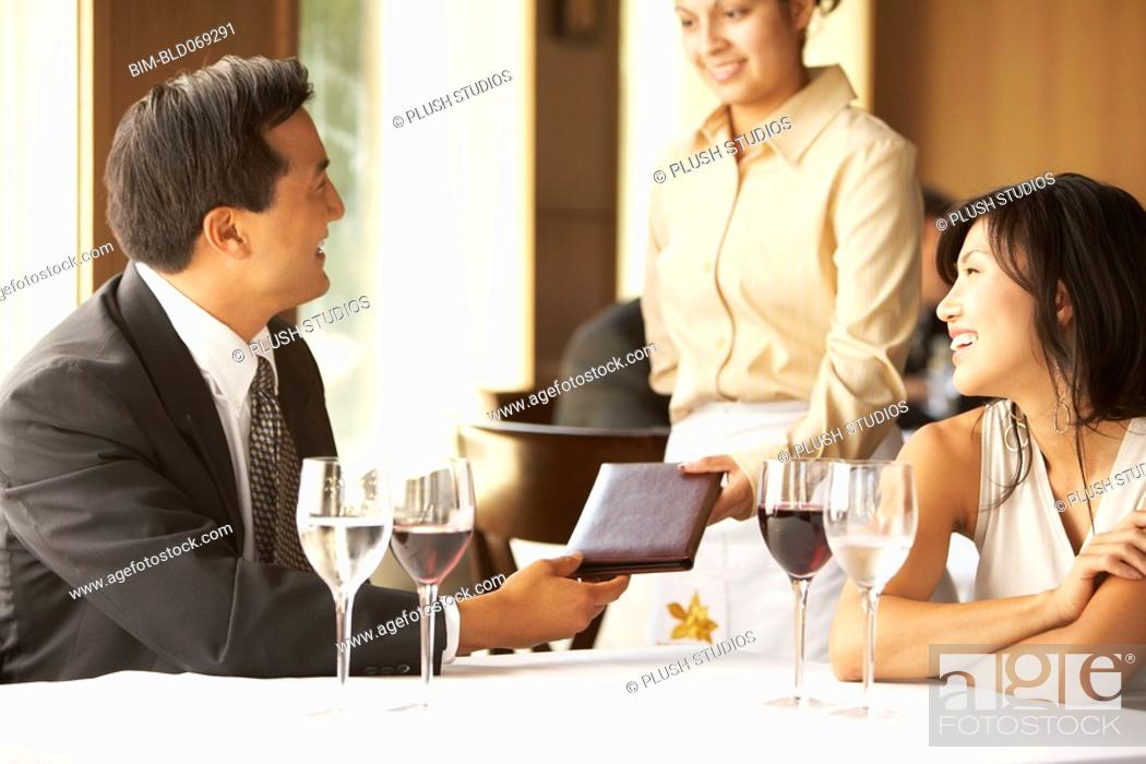 Stock Photo: Asian couple paying bill at restaurant.