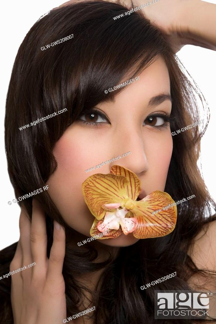 Stock Photo: Portrait of a young woman holding a flower in her mouth.