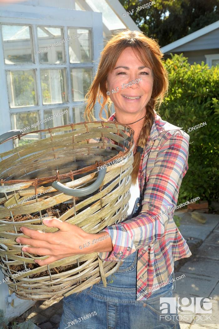 Stock Photo: Woman, 40 yeras old, stand with a basket in her garden in Ystad, Scania, Sweden.