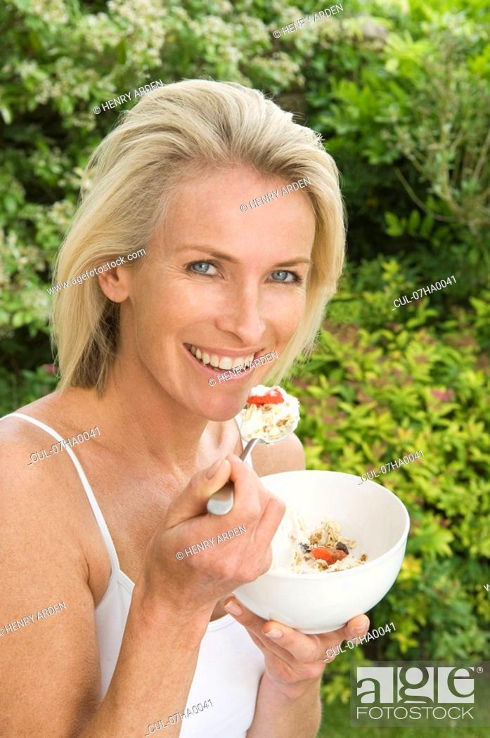 Stock Photo: Woman eating fruit and muesli.