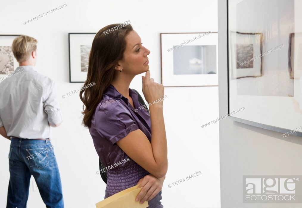 Stock Photo: Woman looking at picture in art gallery.