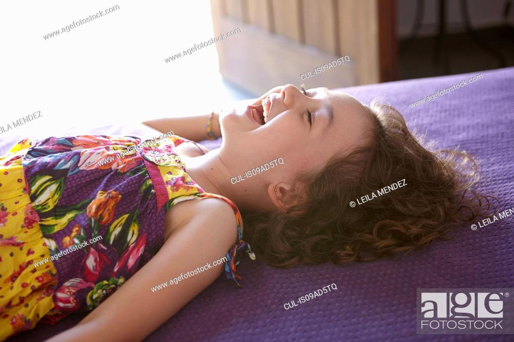 Stock Photo: Girl lying on bed laughing.