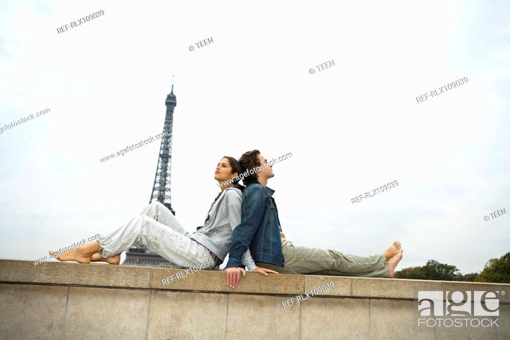 Stock Photo: Young couple sitting back to back on wall, Eiffel tower in background.