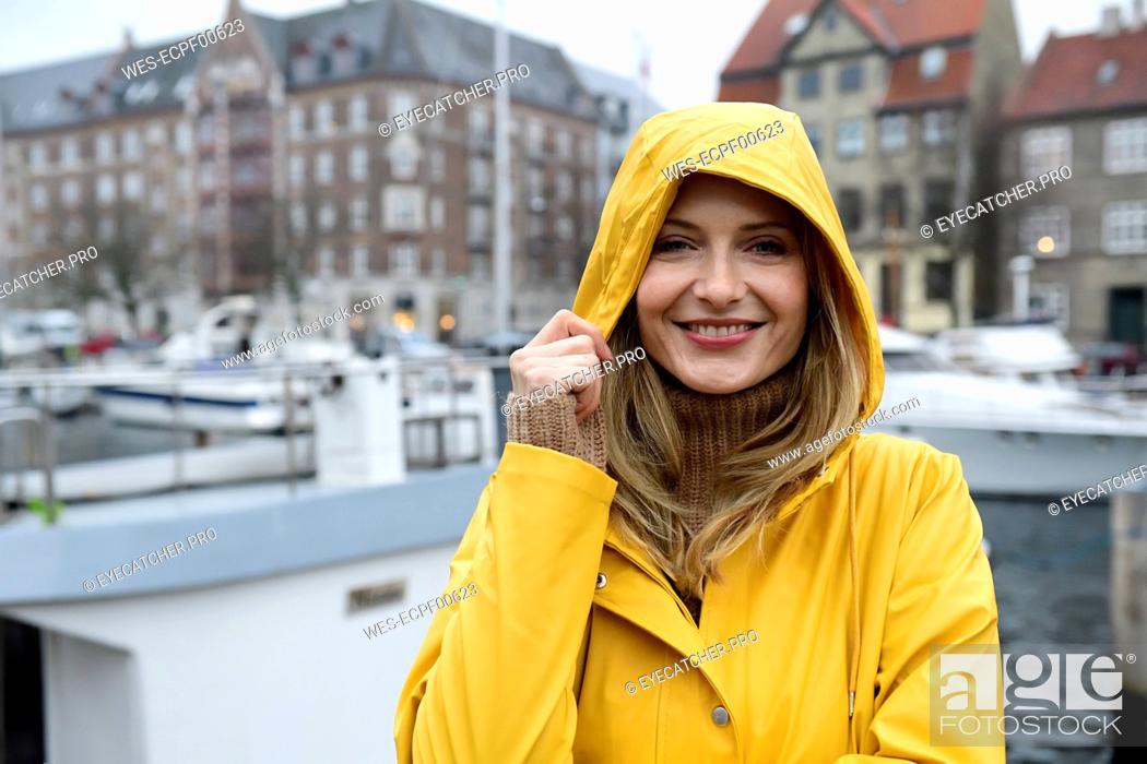 Stock Photo: Denmark, Copenhagen, portrait of happy woman at city harbour in rainy weather.