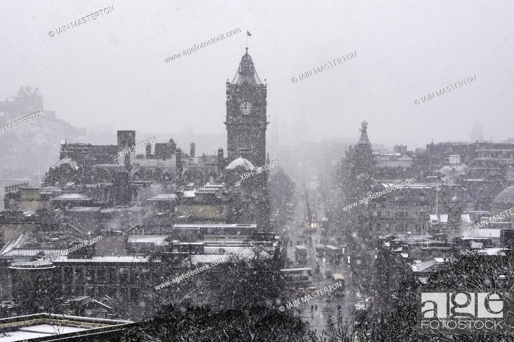 Stock Photo: Snow falls on city of Edinburgh in December. Skyline view of city towards Princes Street from Calton Hill.