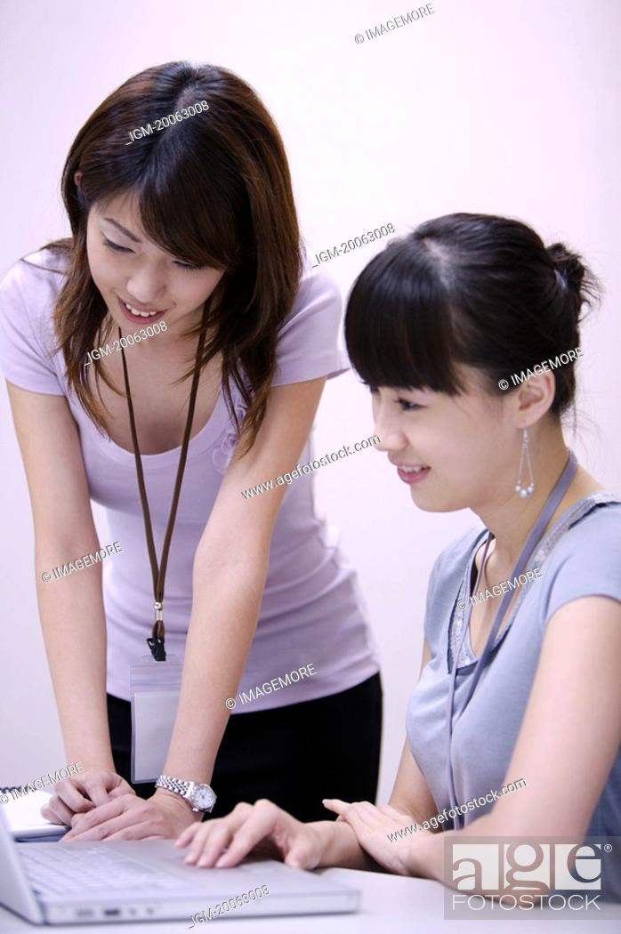 Stock Photo: Two women looking at the laptop together with smile.