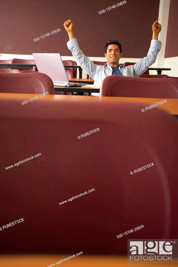 Stock Photo: College student sitting in a lecture hall with his arms raised.
