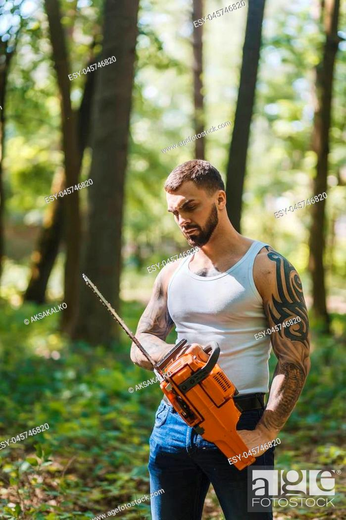 Stock Photo: portrait of aggressive muscular male lumberjack, woodworker with chainsaw in hand, posing.
