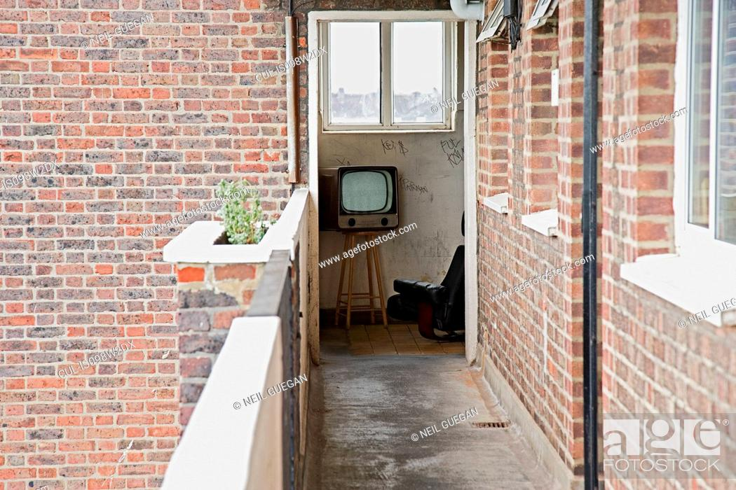Stock Photo: Retro television and armchair seen from apartment balcony.