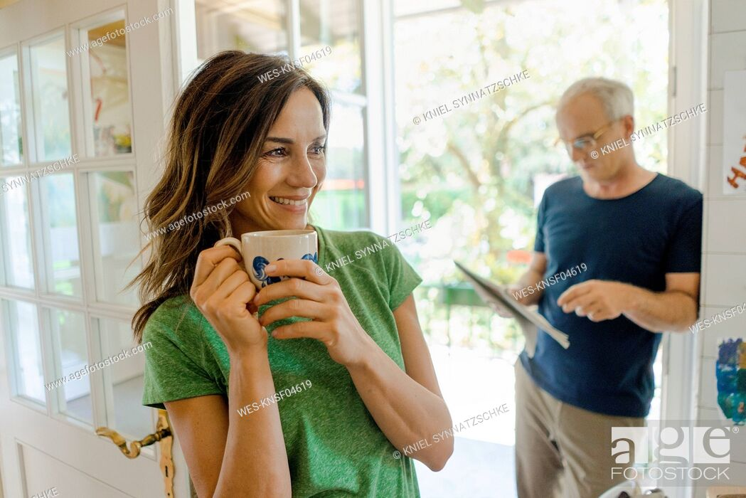 Stock Photo: Mature couple at home with woman drinking coffee and man reading newspaper.