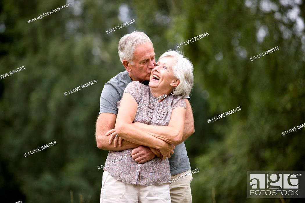Stock Photo: A senior couple standing in a field, laughing.