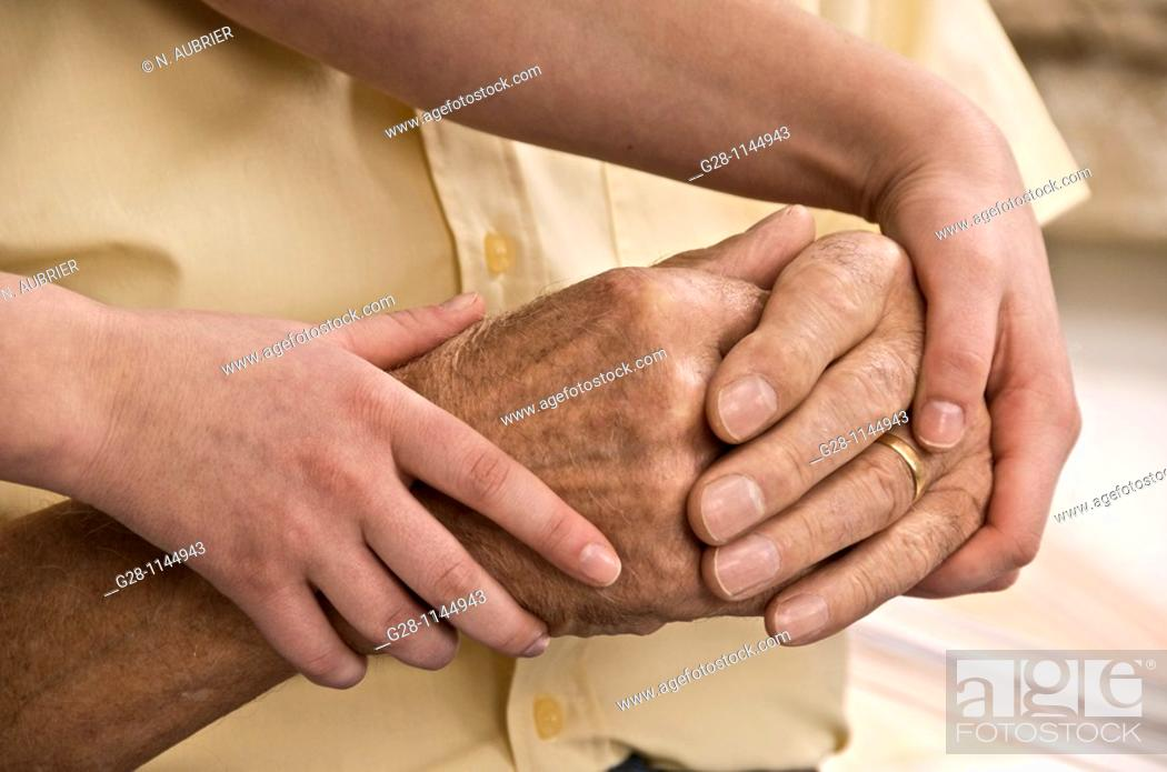 Stock Photo: young person hands helping and comforting a senior man by holding his hands.