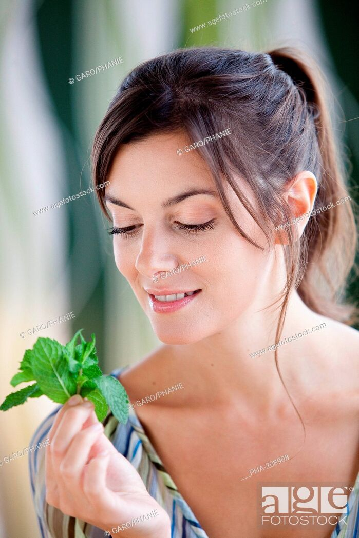 Stock Photo: Woman smelling mint leaves Mentha sp.