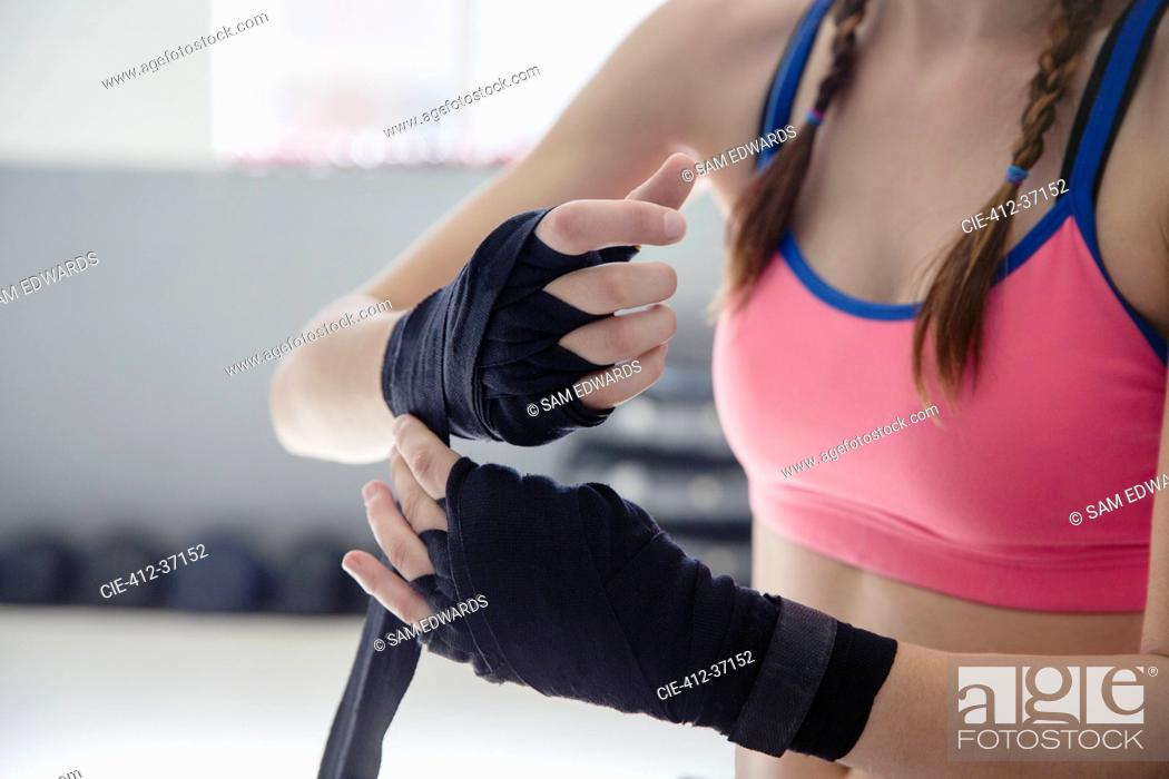 Stock Photo: Close up young female boxer wrapping wrists.