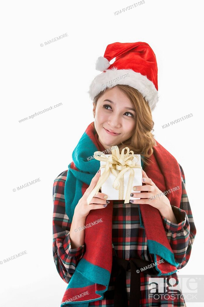Imagen: Young woman holding Christmas gift, wearing Christmas hat.