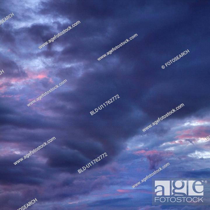 Stock Photo: Dark ominous storm clouds spreading across sky.