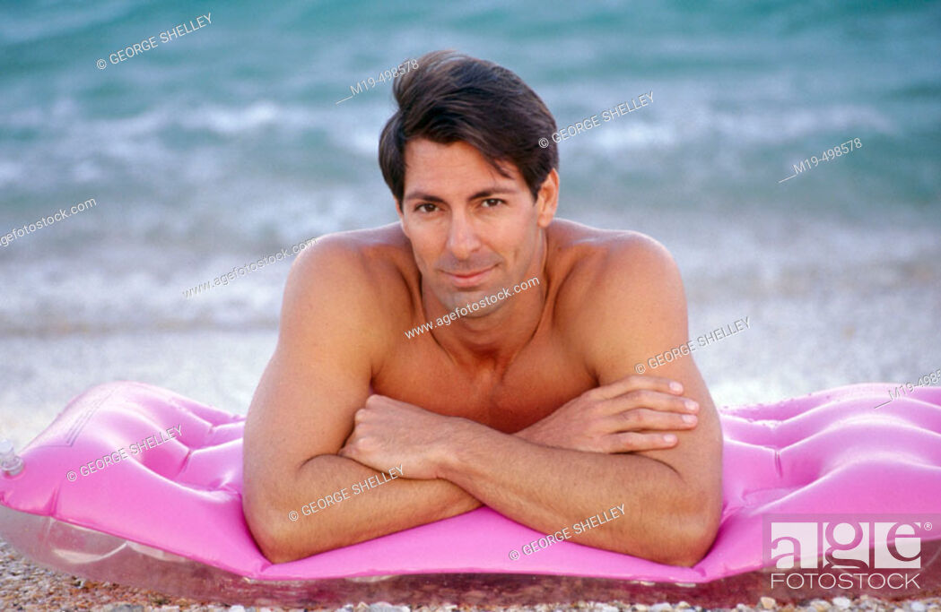 Stock Photo: handsome man lying on the beach.
