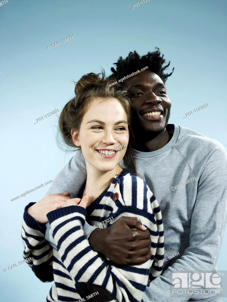 Stock Photo: A smiling young man embracing his smiling girlfriend from behind.