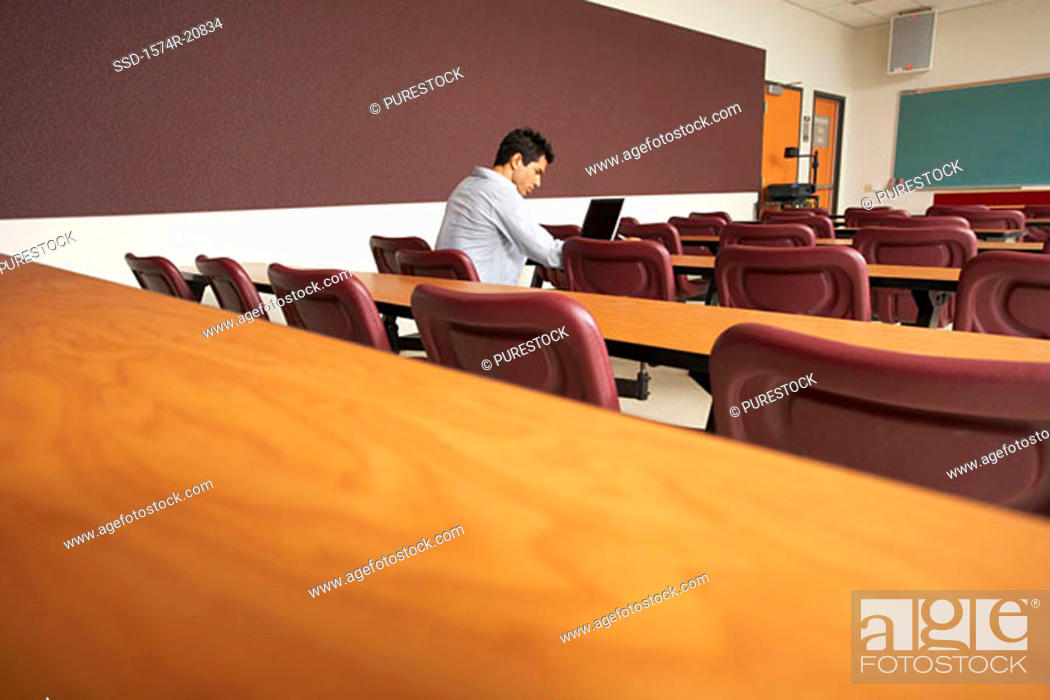 Stock Photo: Side profile of a college student sitting in a lecture hall and using a laptop.