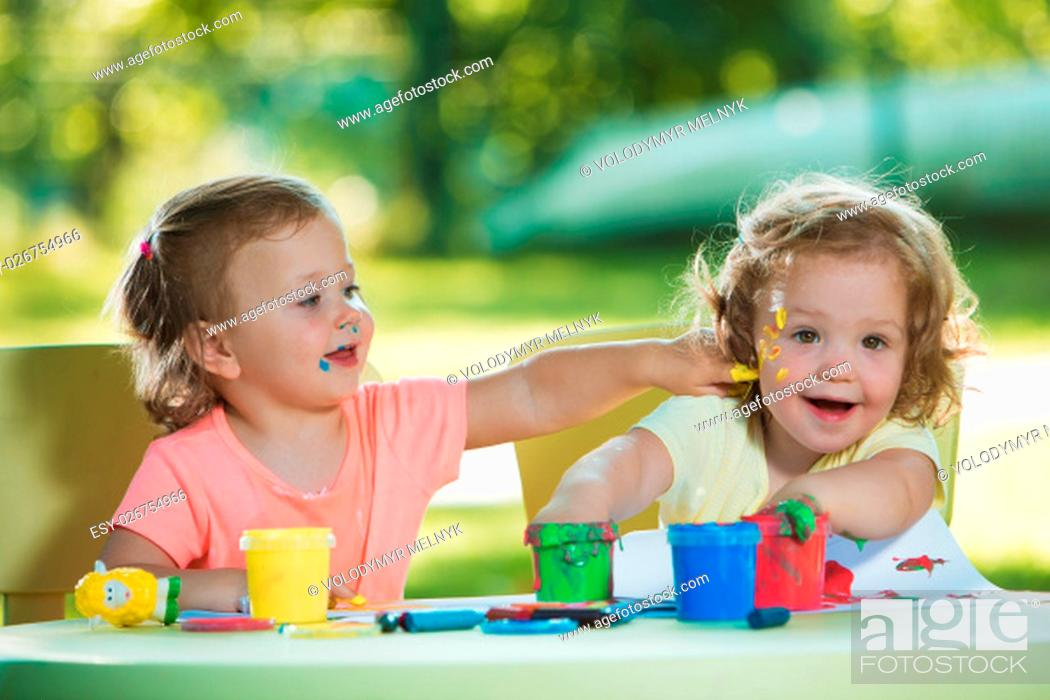 Stock Photo: Two-year old girls painting with poster paintings and sitting at a table together against green lawn.