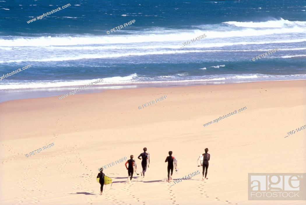 Stock Photo: Surfers run across the sand at Guincho, the famous surfing beach, near Lisbon Portugal.