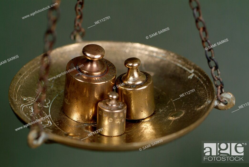 Stock Photo: Group of French copper weights hanging on a scale.