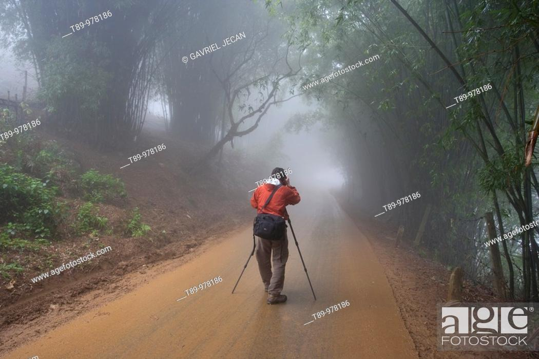 Stock Photo: Vietnam, Sapa, Photographer photographing a misty road up in the mountrains of Northern Vietnam. Model Released.