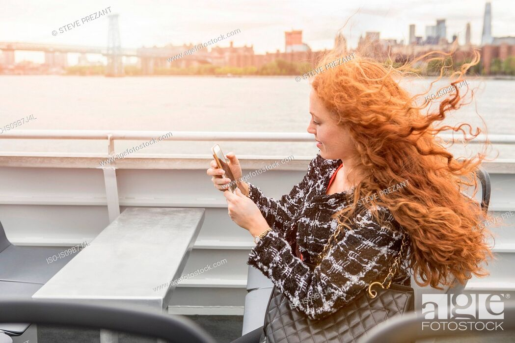 Stock Photo: Young businesswoman on passenger ferry deck looking at smartphone.