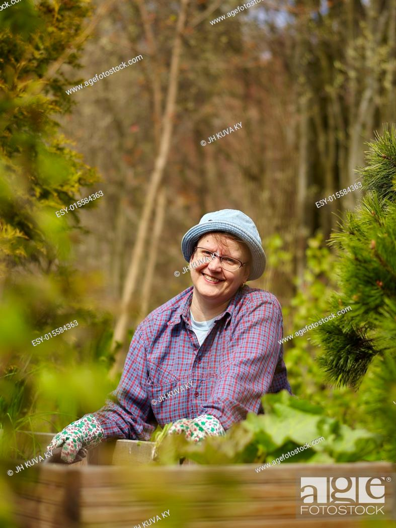 Imagen: Woman weeding in the garden and she use protective gloves.