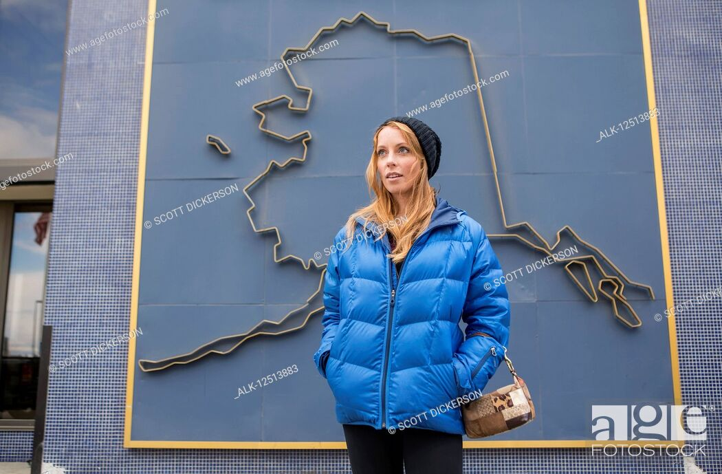Stock Photo: Mid adult woman standing in front of a 3D graphic of the outline of Alaska on a building in downtown Anchorage, South-central Alaska; Anchorage, Alaska.