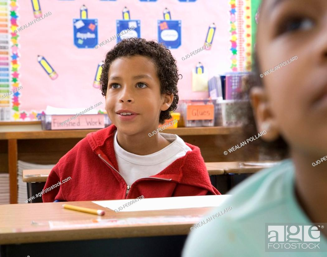 Stock Photo: Boy sitting a desk in classroom.