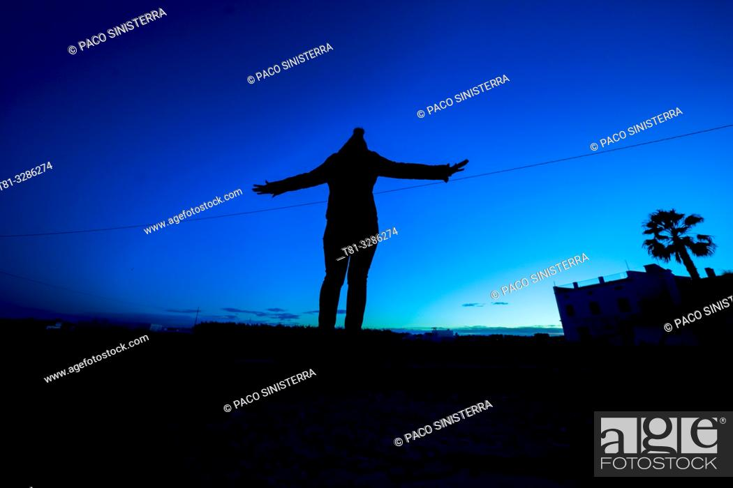 Stock Photo: Silhouette of a girl with open arms against blue sunset sky. Valencia, Spain.