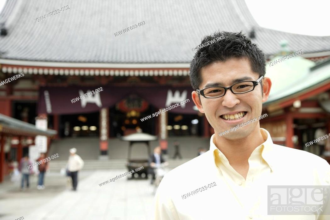 Stock Photo: A young man standing outside temple.