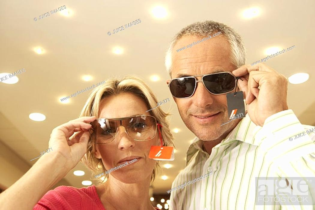 Stock Photo: Mature couple trying on sunglasses in shop, price tag attached, smiling, portrait, low angle view.
