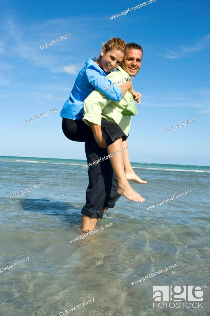 Stock Photo: Side profile of a mid adult woman riding piggyback on a mid adult man on the beach.