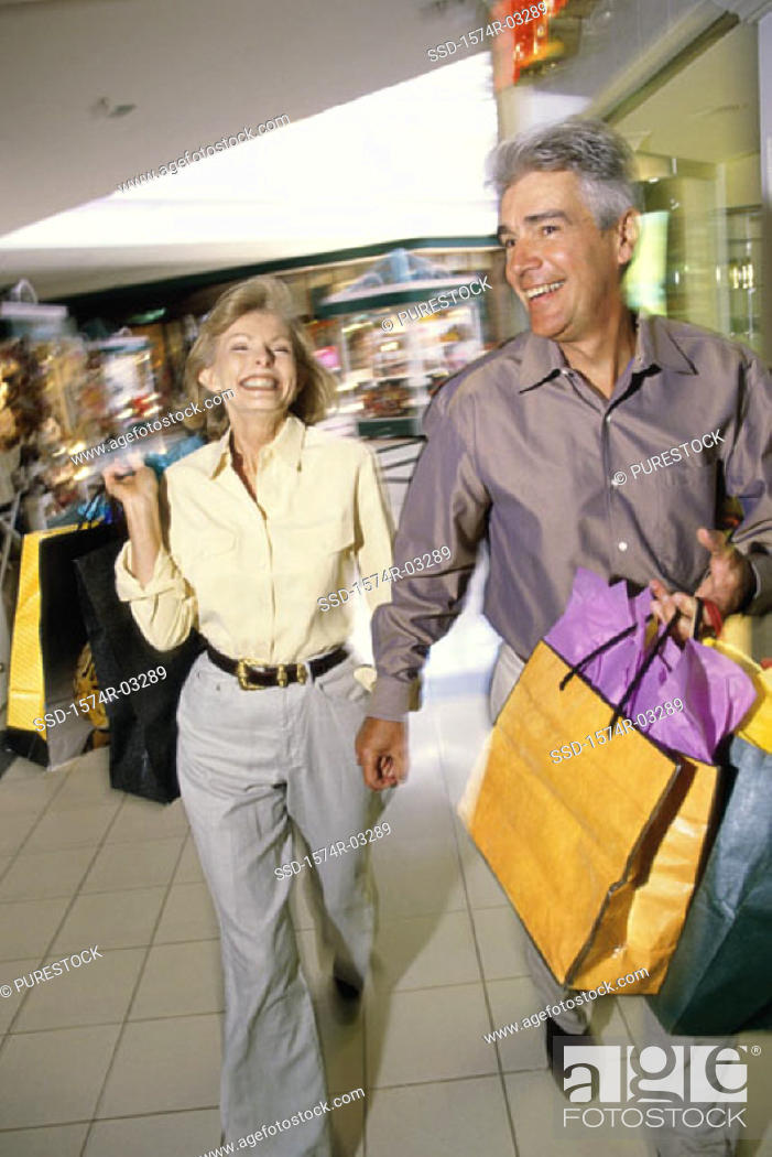 Stock Photo: Mature couple carrying shopping bags.