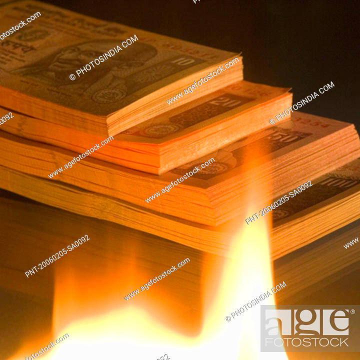 Stock Photo: High angle view of a stack of Indian banknotes of different denominations near a flame.